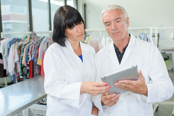 Man and woman in dry cleaners looking at tablet
