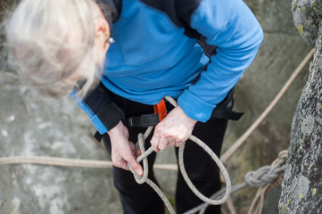 Climber woman in safety harness tying rope in bowline knot and preparing to climb
