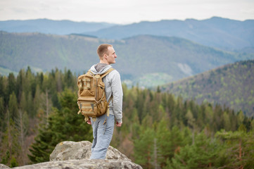 Male hiker with backpack stands on rock with back to the camera and looking into the distance. Forest and mountains in background