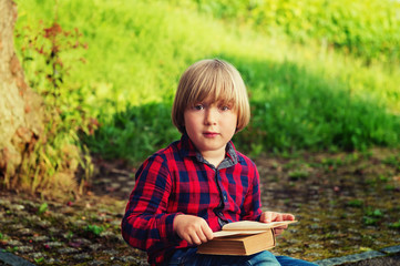 Sweet little boy reading old book in park, wearing red and blue plaid shirt. Toned image
