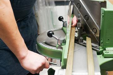 Craftsman working on frame in frame shop. Professional framer ha