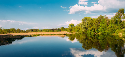 River Landscape With Clouds Reflected In The Water. Sunny Summer