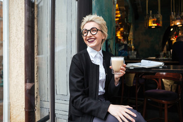 Close-up portrait with smiling girl holding cup of coffee