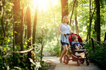Pregnant woman walking with child in nature