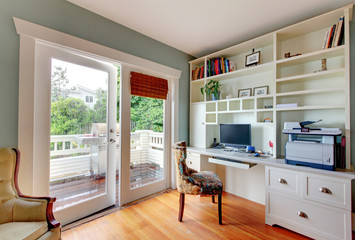 Home office with white open shelves, desk and hardwood floor.