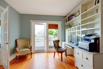 Home office with blue walls and hardwood floor.