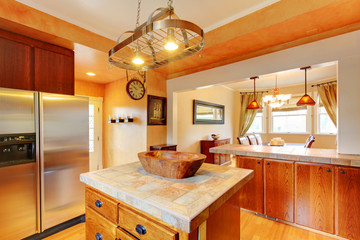 Kitchen and dining room interior with brown wooden cabinets and dining table set.
