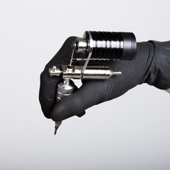 close-up of Tattooist hands in black gloves with tattoo machine