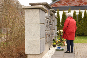 Ältere Frau steht vor Urnenwand mit Grabschmuck