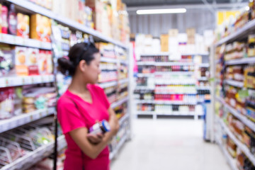 The blurred of picture woman is shopping in the supermarket.
