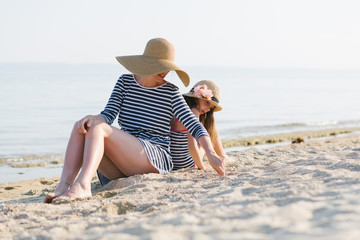 Mother and daughter sitting on the beach