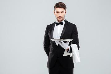 Fototapeta Handsome yong waiter in tuxedo and gloves holding empty tray obraz