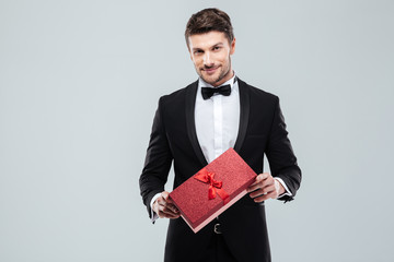 Confident attracive man in tuxedo standing and holding gift box