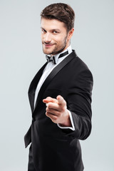 Happy confident man in tuxedo with bowtie pointing on you