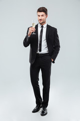 Smiling handsome young businessman standing and holding glass of champagne