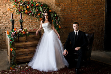 newlyweds in a beautiful room full of flowers. Bride stands at the chest. Bride sitting in a leather chair