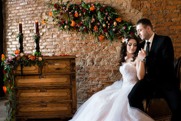 A sitting bride holding her man's hand and smiling, chest of drawers and a brick wall with flowers on the background