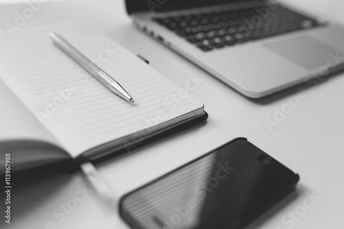 Photo noir et blanc calepin ouvert avec un stylo smartphone et