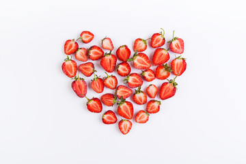 Fresh strawberries halves arranged in a heart on a white background