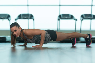 Healthy Young Woman Doing Push-ups On Floor