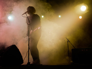 Silhouette of guitar player on stage.