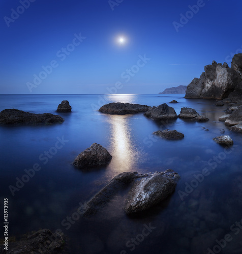 Wall mural Colorful night landscape with full moon, lunar path and rocks in summer. Mountain landscape at the sea.