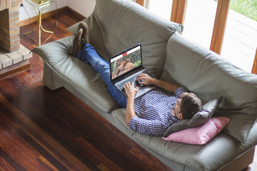 Young man lying comfortably on the sofa while using the laptop with travel agency website on screen. View from top. All screen graphics are made up.
