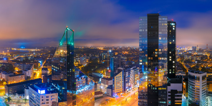 Aerial panorama of modern business financial district with tall skyscraper buildings illuminated at night, Tallinn, Estonia