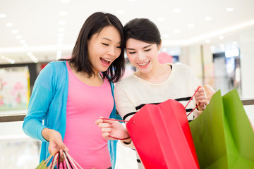 Two women looking inside shopping bag
