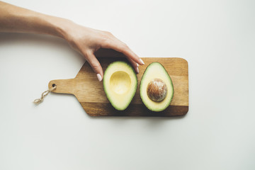 Close-up image of female hand holding fresh avocado on wooden board in the white background, healthy lifestyle concept