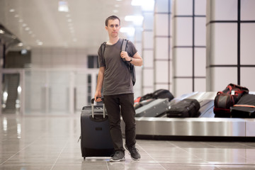 Young man got luggage at conveyor belt