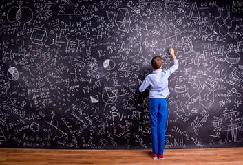 Boy against big blackboard with mathematical symbols and formula