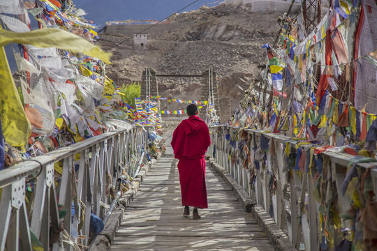 A monk walks onthe bridge pathway surrounded by colorful tibetan