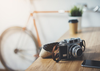 Close-up of vintage camera on the wooden table, modern home design in the blurred background, hipster orange bike, film effects, blank space with copy space for your design or content