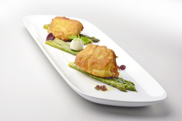 Fish dish Salt cod breaded Milanese style with asparagus