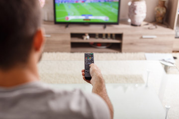Man with remote control watching football match