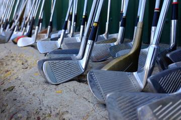 Row of Many Old Used Golf Clubs for Sport