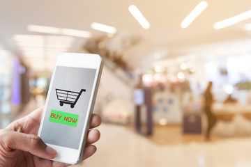 Hand holding smart phone with blurred shopping mall background -