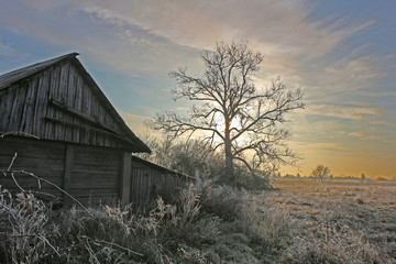 Abandoned barn in rural outback to the winter landscape of the rising sun.