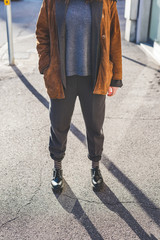 From the neck down view of young woman wearing balck pants, stripes socks, jumper, and jacket - hipster, stylish, contemporary concept