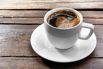 Cup of fresh coffee on wooden background