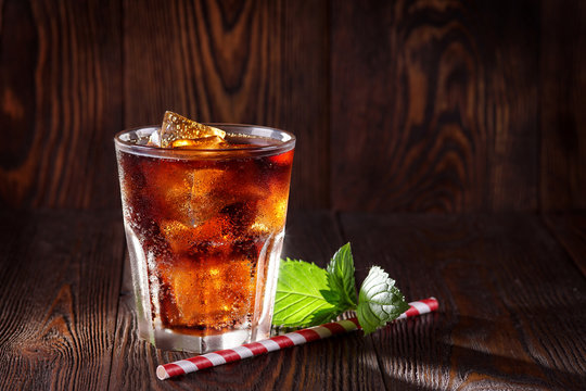 Cola drink. Cola with ice in a glass on a background of vintage boards