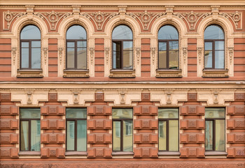 Several windows in a row on facade of urban apartment building front view, St. Petersburg, Russia.