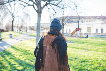 Back view of a young millennial woman walking in a city park, wearing hat, scarf and jacket - winter, relax concept