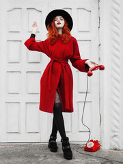 red-haired girl with red lips and pale skin with a black hat and red coat in an elegant, stylish woman in black boots in tights with a red rotary phone, the phone receiver in hand, on white background