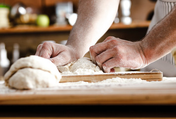 Close up of male baker hands kneading dough and making bread.