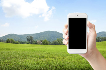 Selfie with mobile smart phone on green park and sky background