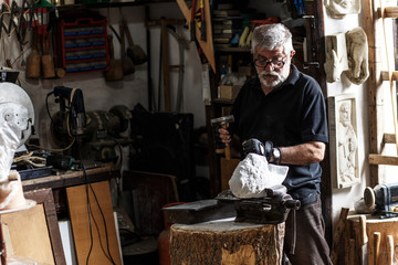 Senior sculptor working on his marble sculpture in his workshop with hammer and chisel
