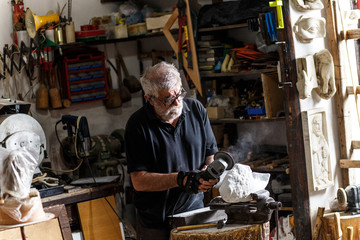 Senior sculptor working on his marble sculpture in his workshop with grinder.