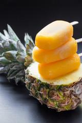 Column of pineapple sorbet ice cream popsicles.